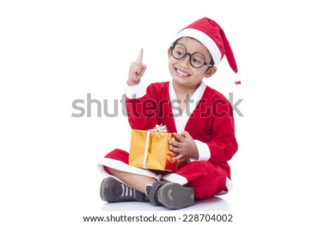 Little boy wearing Santa Claus uniform with gift and pointing up.  - stock photo