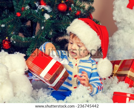 Little boy wearing Santa hat holding his first christmas present - stock photo