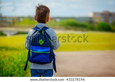 Little boy with a backpack go to school. Back view. - stock photo