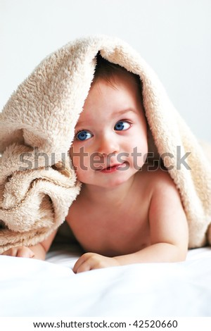 Little boy with a blanket on head - stock photo