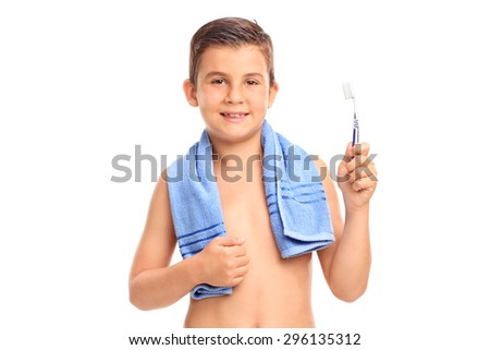 Little boy with a blue towel around his neck holding a toothbrush and looking at the camera isolated on white background