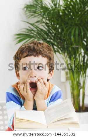 Little boy with a book./Tired schoolboy studying in home. - stock photo