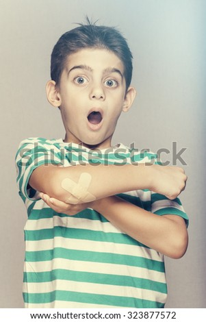 Little boy with a bruised elbow. Cross processed image - stock photo
