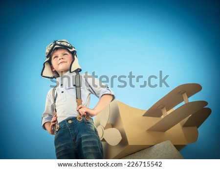 Little boy with a cardboard airplane outdoors - stock photo