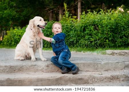 Little boy with a golden retriever - stock photo