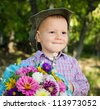 Little boy with a large bunch of colourful flowers for his sweetheart on Valentines day - stock photo