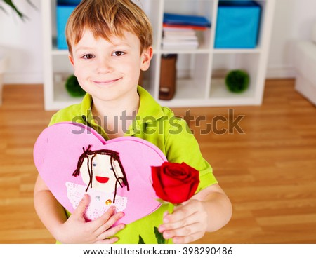 Little boy with a red rose and a card for his mother - stock photo