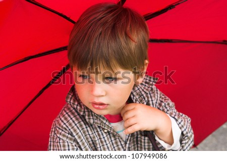 Little boy with a red umbrella in his hand is listening to the rain. His face collected. - stock photo
