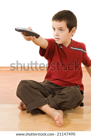 Little boy with a remote control sitting on the floor and watching tv - stock photo