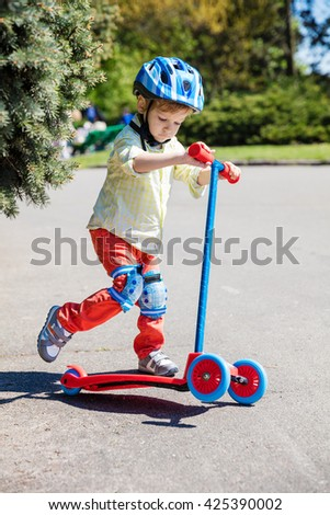 Little boy with a scooter outdoors - stock photo