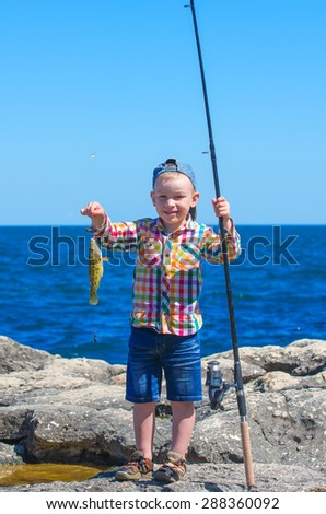 "Little boy with a smile holding a fishing rod with his first catch - ""Symphodus tinca"". Family composition"