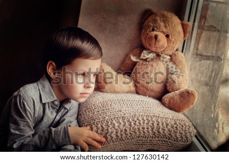 little boy with a toy on a knitted pillow looking out the window - stock photo