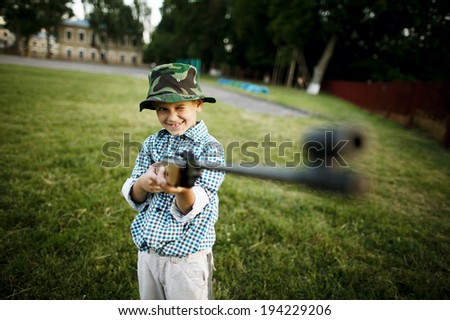 little boy with airgun outdoors - stock photo