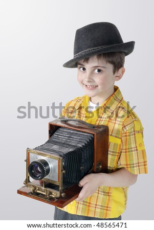 Little boy with an old camera on the grey background - stock photo