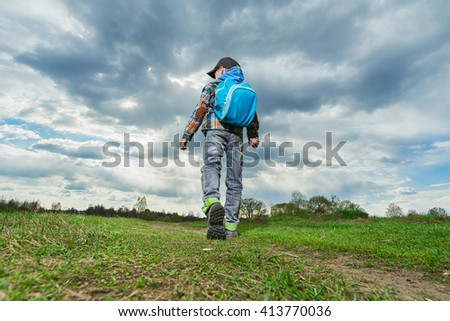 Little   boy with backpack walking in nature. Travel concept. - stock photo
