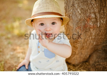 Little boy with big brown eyes and a hat sucks a finger, on the background of sunset in summer, close-up - stock photo