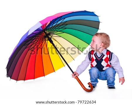 Little boy with big multicolored umbrella sitting on white