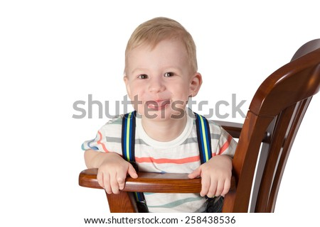 Little boy with blond hair sitting on a chair and showing tongue closeup isolated on a white background - stock photo
