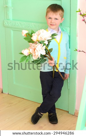 little boy with bouquet of big white flowers at door indoors - stock photo