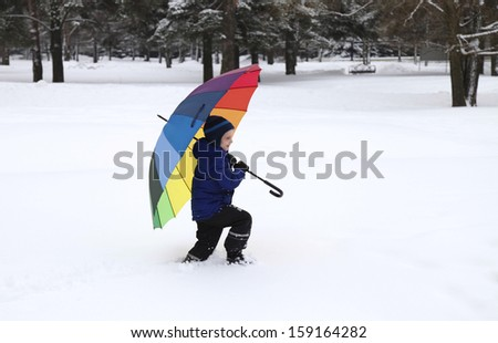 Little boy with bright colorful umbrella in snow park - stock photo