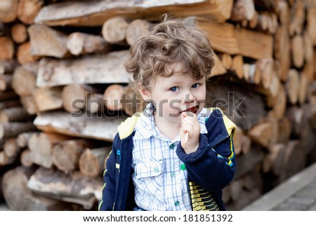 little boy with candy on a background of wood