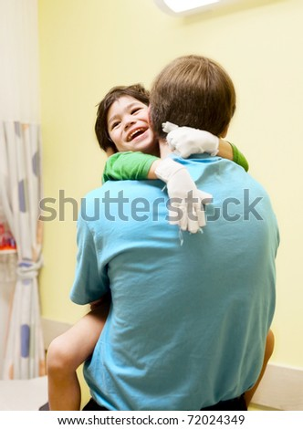 Little boy with cerebral palsy in doctor's office, laughing with his father - stock photo