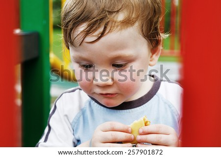 Little boy with cheese and cracker playing on playground - stock photo