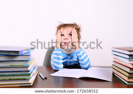 little boy with disheveled hair  sitting at a desk and looking up. boy 5 years. on the desk a lot of books. photo taken on a light background - stock photo