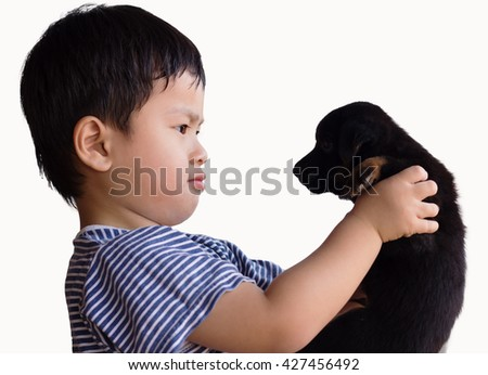 Little boy with dog puppy mascot mini on white background, kid playing black puppy on white, cute boy holding a little dog, - stock photo