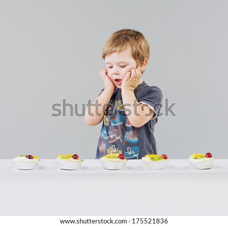 Little boy with fruit cake - stock photo