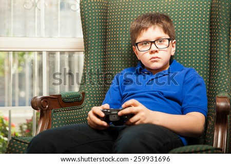 Little boy with glasses relaxing and playing video games at home - stock photo