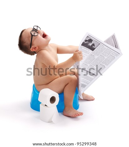 Little boy with glasses, sitting on potty and having fun with newspaper - stock photo