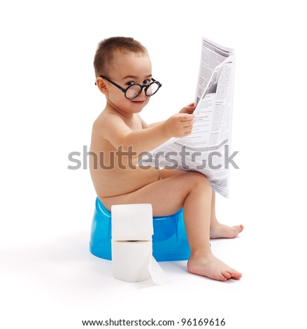 Little boy with glasses, sitting on potty and reading newspaper - stock photo