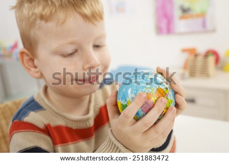 Little boy with globe in a hand - stock photo