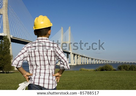Little boy with gloves and a helmet looking to a bridge