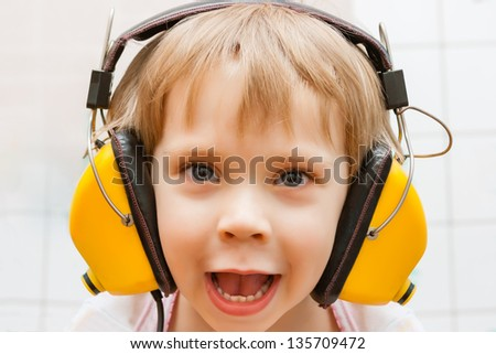 Little boy with headphones listening to music - stock photo