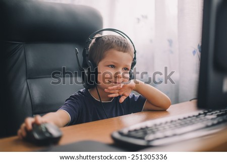 little boy with headset using computer, early education and learning - stock photo
