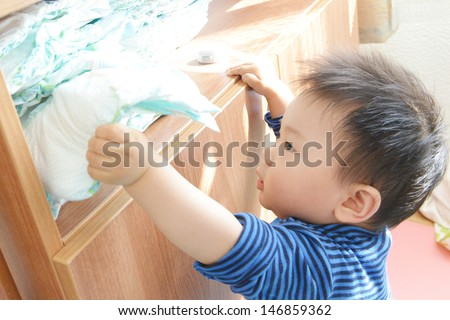 little boy with his diaper in hand - stock photo