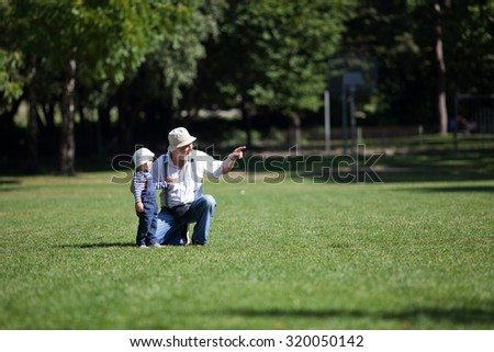 Little boy with his grandfather walking in the park - stock photo