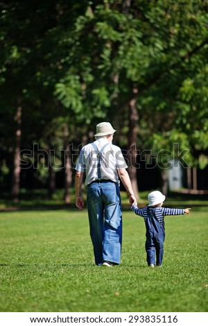 Little boy with his grandpa walking in the park - stock photo