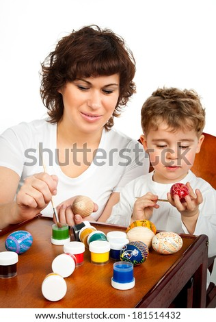 little boy with his mother paint the Easter eggs on white - stock photo