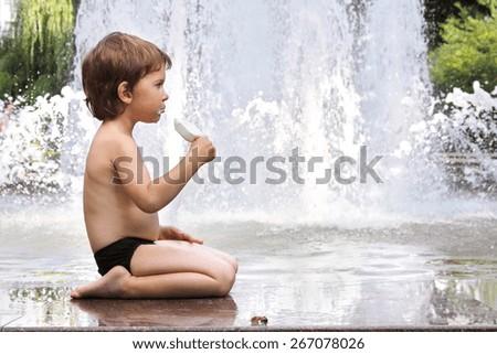 little boy with ice cream near the fountain - stock photo