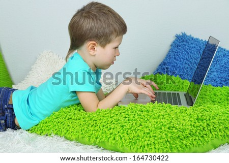 Little boy with laptop on bed  - stock photo