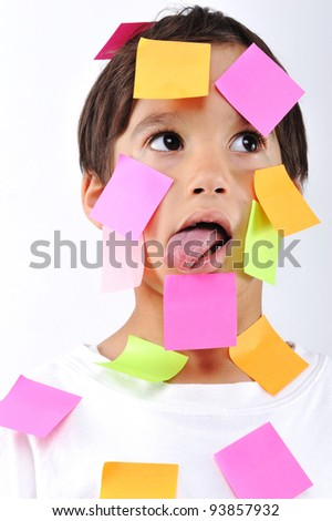 Little boy with memo notes on his face - stock photo