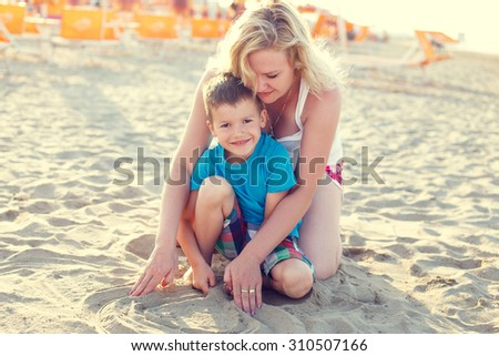 Little boy with mom on beach, parenting, summer holiday - stock photo