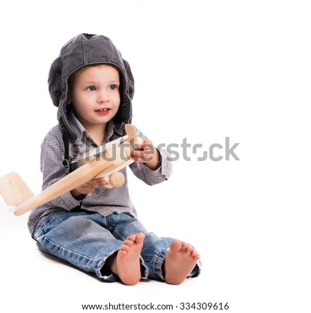 little boy with pilot hat playing toy plane isolated on white background