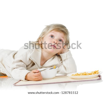 little boy with plates of yellow cereals on white - stock photo