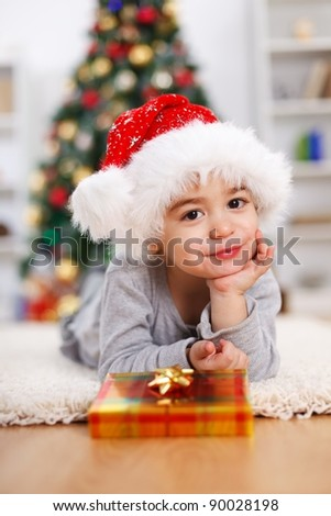 Little boy with present, prop his head, laying in front of Christmas tree - stock photo