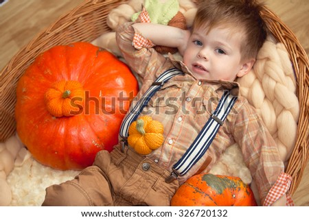 Little boy with pumpkin on the farm