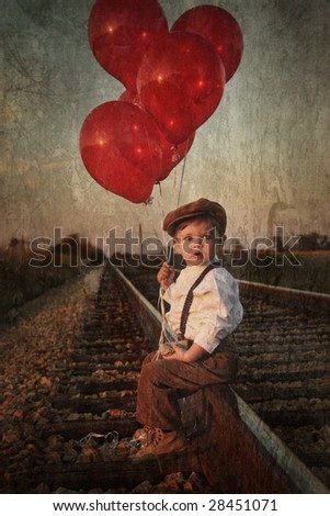 little boy with red balloons on railroad tracks - stock photo